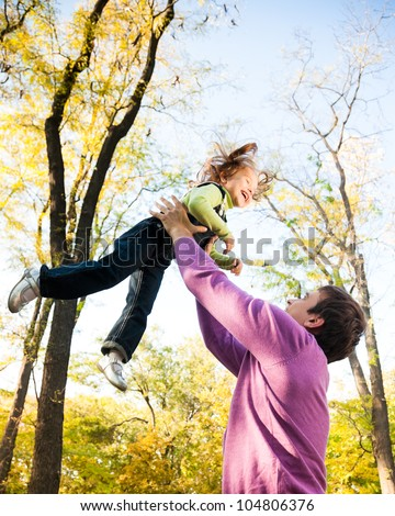 Man with child having fun in autumn park. Focus on man