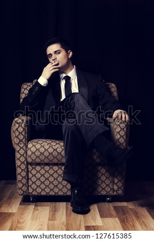 Man with cigarette sitting in vintage armchair
