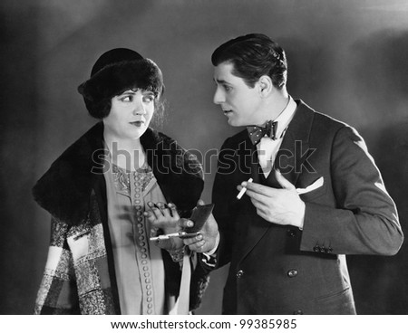 Man with cigarettes talking to woman