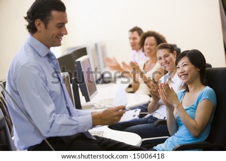 Man with clipboard giving lecture in applauding computer class