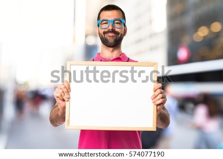 Man with colorful clothes holding an empty placard