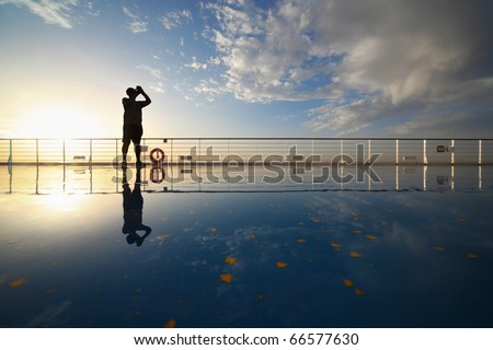 man with compact photo camera shooting morning sky from deck of cruise ship. reflection in deck.