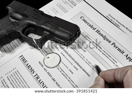 man with concealed carry permit application and pistol gun firearm