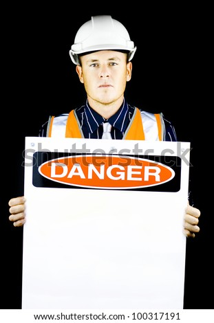 Man with construction helmet holding blank 'danger' sign on black background