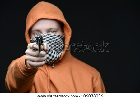 Man with covered face with gun aiming