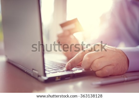 Man with credit card using a laptop computer for internet shopping