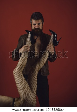 Man with cunning face holds female legs. Lady in fishnet tights and high heeled shoes lays on burgundy background. Hipster with beard holds sexy naked girl full of desire. Intimacy and desire concept. #1045525864