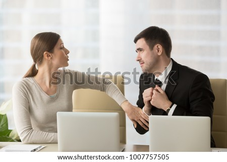 Man with deliberately sad facial expression asking female coworker to help with difficult project to leave work earlier, inviting colleague to date. Businesswoman refuses in request of foolish admirer #1007757505