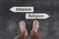 man with dirty feet in slippers is standing on asphalt next to arrow signs of words atheism and religion