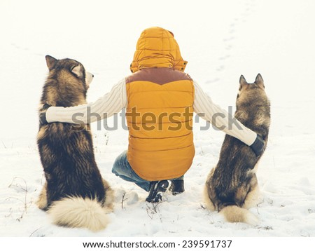 Man with dog Huskies back sit on snow. Friendship animal dog and man