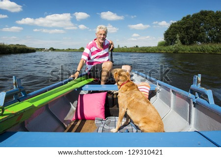 Man with dog in boat at the river