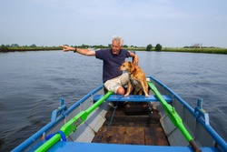 Man with dog in whisperboat at Dutch river