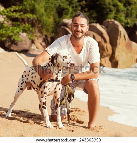man with dog on the tropical beach