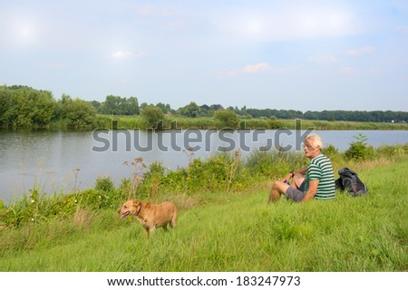Man with dog sitting in nature river landscape