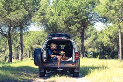 Man with dog sitting in off road car boot in forest. Freedom and traveling couple.