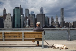 Man with dog sitting on a bench an enjoys the view of the Manhattan skyline, New York City