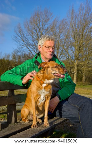 Man with dog sitting on a bench in winter sun