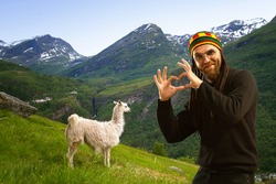 man with dreadlocks holds hands in a heart shape. lamas in the mountains. scenic spots in nature.