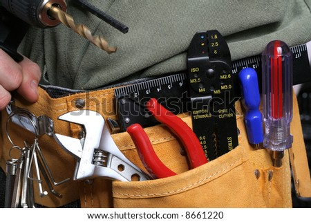 man with drill and tool belt