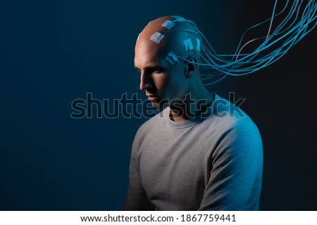 man with electrodes in his head is a futuristic concept of virtual reality and mind control. Neuro interface, contact of biological and mechanical Stockfoto ©