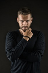 Man with evil look isolated on dark background. Macho touching his beard. Man in black jumper wearing beaded bracelet. Devil with cunning face, hidden danger concept.