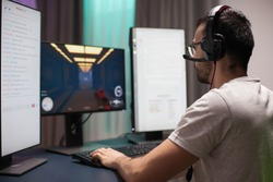 Man with eyeglasses wearing headphones while playing shooter games and reading streaming chats on dual screen setup