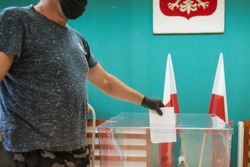 Man with face mask and gloves, due to pandemic Covid-19, throwing a card with a voteto the ballot box during  elections. In the backround polish emblem and flag