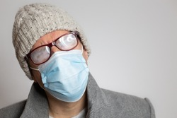 man with face mask,foggy glasses and grey blazer close up with copy space. horizontal