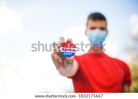 Man with face mask showing I voted today badge at ballot box. Stock photo ©