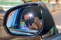 MAN WITH FACIAL PROTECTION MASK TAKING PHOTO WITH FLASH FROM INSIDE THE CAR AND REFLECTED IN THE REAR VIEW MIRROR