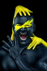 Man with female hands on the body. Bodybuilder athlete with yellow face art and body paint. Colorful portrait of the guy with bodyart.
