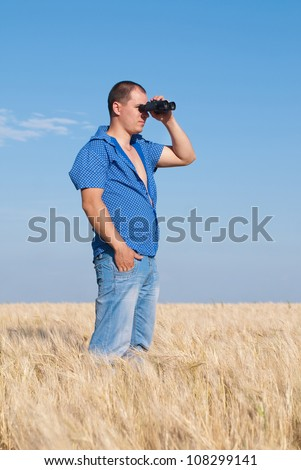 Man with field-glass in hand on wheat field