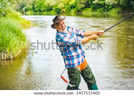 Man with fishing rods on river berth. Angler. Fly fishing is most renowned as a method for catching trout and salmon. Concepts of successful fishing #1457515400