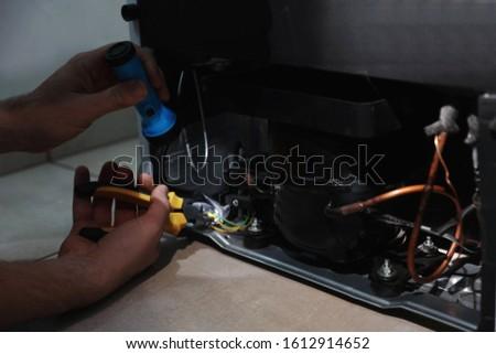 Man with flashlight fixing refrigerator indoors, closeup