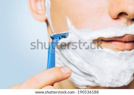 Man with foam on his face is shaving with razor, close-up