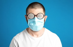 Man with foggy glasses caused by wearing disposable mask on blue background. Protective measure during coronavirus pandemic