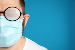 Man with foggy glasses caused by wearing disposable mask on blue background, space for text. Protective measure during coronavirus pandemic