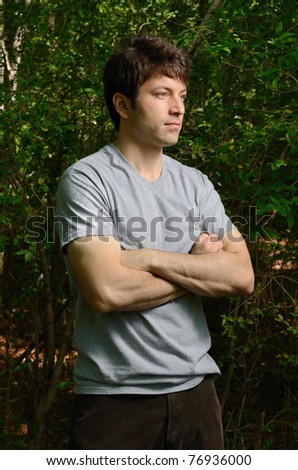 man with folded arms and leafy background.
