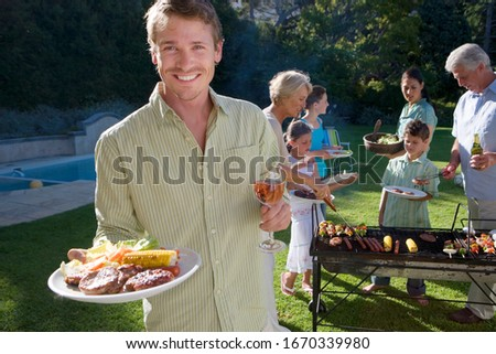 Man with food at multi-generation family barbecue in garden at home