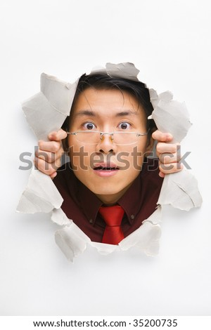 Man with funny expression gazing from hole in wall