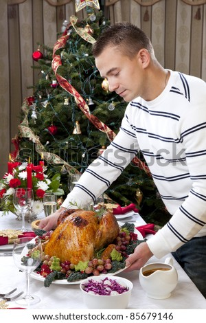 Man with Garnished Thanksgiving roasted turkey to celebrate traditional family dinner with salad, fruits, vegetables, wine and champagne glasses on Christmas tree background
