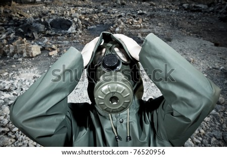Man with gas mask holding his head