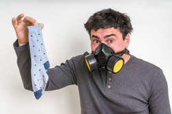 Man with gas mask is holding dirty stinky sock - unpleasant smell concept