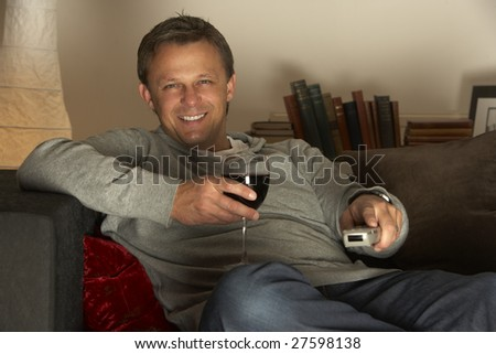 Man With Glass Of Wine Watching Television - stock photo