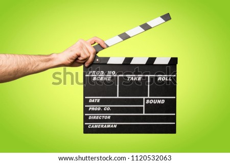 Man with glasses holding a clapperboard on colorful background #1120532063