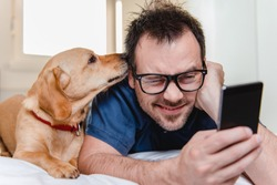 Man with glasses in blue shirt laying on the bed with the dog and using smart phone.