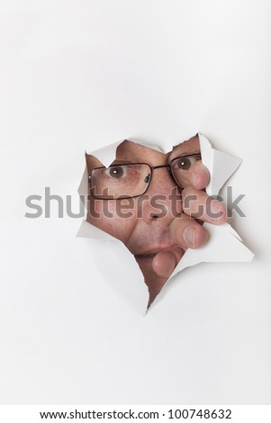 Man with glasses looking through a paper hole