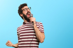 Man with glasses singing with microphone on colorful background