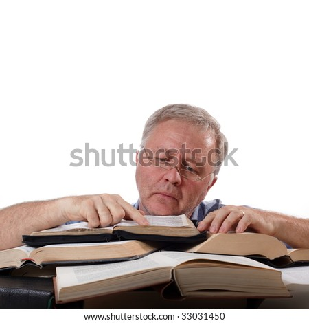 Man with glasses working with many books
