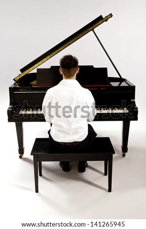 Man with Grand piano wearing white shirt and black pants sitting at piano bench.
